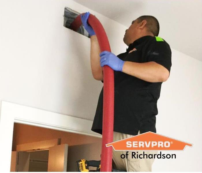 man on ladder cleans air duct vent in home with red hose